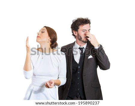 Closeup portrait young couple, man, woman. Female happy smiling, enjoying aroma, male unhappy pinching his nose, disgust face, hates smell isolated white background. Perception contrast, body language - stock photo