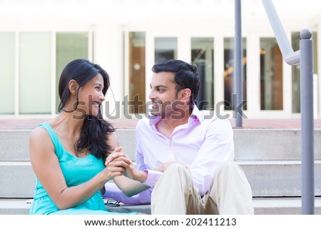 Closeup portrait, young couple sitting on stairs, looking at each other in love, isolated outdoors background - stock photo