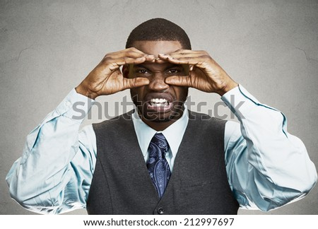 Closeup portrait young, curious funny man, looking through his fingers like binoculars, searching something, unhappy disgusted with future forecast isolated grey wall background. Human face expression - stock photo