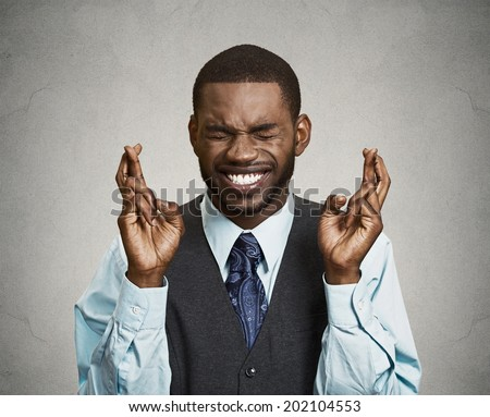 Closeup portrait young funny guy, business man crossing fingers, wishing, hoping for best, miracle isolated black, grey background. Positive human emotions, facial expressions, feelings, attitude - stock photo