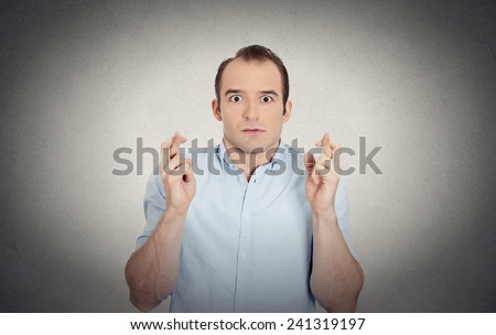 Closeup portrait young funny looking guy, sarcastic, anxious business man crossing fingers, wishing, hoping for luck, miracle isolated grey wall background. Emotions, facial expressions, feelings - stock photo