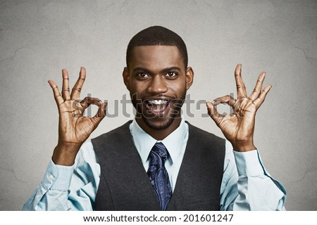 Closeup portrait young handsome, happy, smiling, excited man, corporate employee, worker giving OK sign with fingers, isolated black grey background. Positive human emotion facial expressions, symbol - stock photo