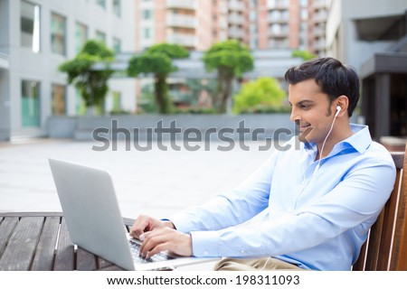 Closeup portrait, young handsome man in blue shirt typing away, listening to headphones, browsing digital computer laptop, isolated background of sunny outdoor, green trees, office background - stock photo