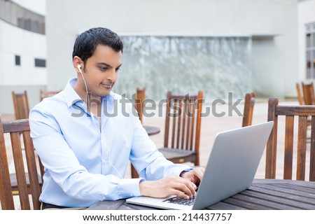 Closeup portrait, young handsome man in blue shirt typing away, listening to headphones, browsing digital computer laptop, isolated background of sunny outdoor, brown chairs background - stock photo