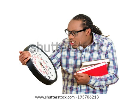 Closeup portrait young handsome man, with glasses, holding books, wall clock, anxious in anticipation of finals test, isolated white background. Negative facial expressions, feeling, emotion, reaction - stock photo