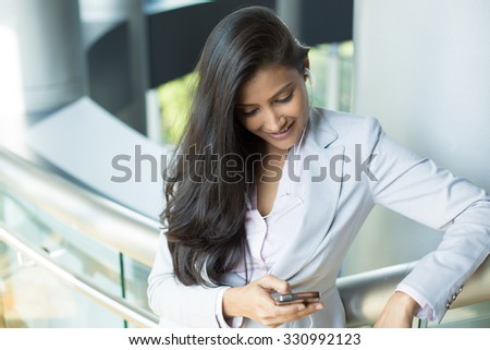 Closeup portrait, young happy business woman in gray white suit dress standing, checking her cellphone, listening to music, isolated on indoors office background. Corporate life success.  - stock photo