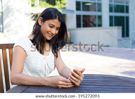 Closeup portrait, young happy business woman in white dress sitting, checking her cellphone, isolated on background of building, chair and table, on a sunny summer day. Business communication - stock photo