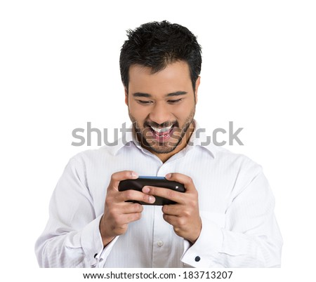 Closeup portrait young, joyful, handsome, nice, friendly man looking and smiling on cell phone watching sports game match or reading an sms, e-mail, viewing latest news, isolated white background - stock photo