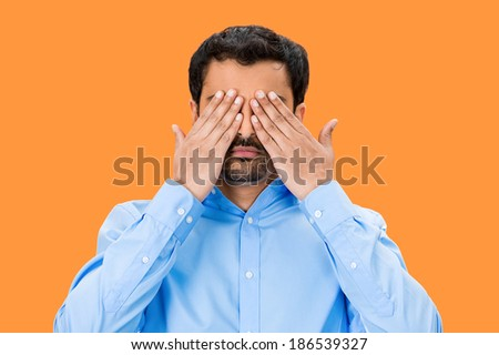 Closeup portrait, young male, shy man closing covering eyes with hands can't see, hiding, isolated orange background. See no evil concept. Negative human emotion, facial expression feeling, reaction - stock photo