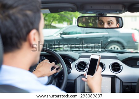 Closeup portrait, young man in blue polo shirt driving in black car and checking his phone, then shocked almost about to have traffic accident, isolated interior car windshield background  - stock photo