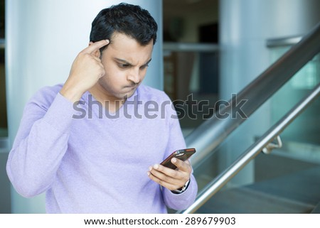 Closeup portrait, young man in purple sweater dumbfounded, flabbergasted about what he sees on cellphone, racking brain, isolated indoors office background - stock photo