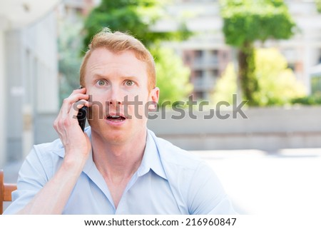 Closeup portrait,  young man, shocked surprised, wide open mouth, by what he hears on the cell phone, isolated outdoors building background. - stock photo