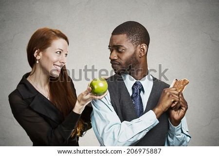 Closeup portrait young nutritionist woman trying to convince stubborn man to eat healthy apple fruit instead of sweet cookie, isolated black background. Negative emotions, facial expressions, feeling - stock photo
