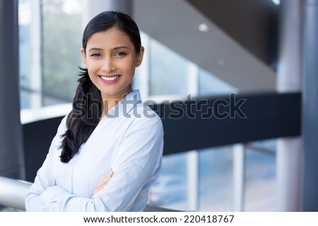 Closeup portrait, young professional, beautiful confident woman in blue shirt, arms crossed folded, smiling isolated indoors office background. Positive human emotions - stock photo