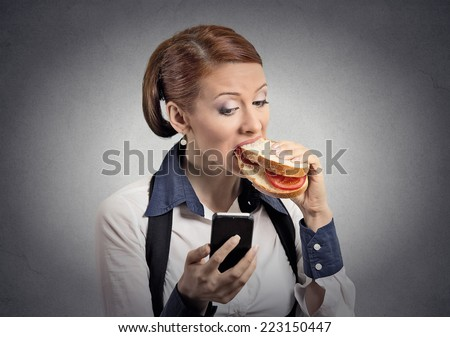 Closeup portrait young serious corporate business woman deal maker reading news message on smart mobile phone holding eating sandwich isolated grey background. Human face expression. Social media app - stock photo