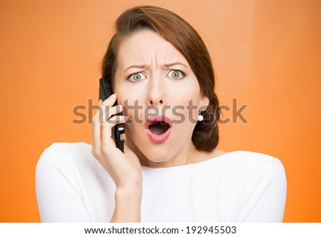 Closeup portrait young shocked business woman, corporate employee talking on cell phone, having unpleasant, bad conversation, isolated orange background. Negative emotion, facial expressions, reaction - stock photo