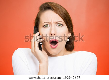 Closeup portrait young shocked business woman, corporate employee talking on cell phone, having unpleasant, bad conversation, isolated red background. Negative emotion, facial expressions, reaction - stock photo