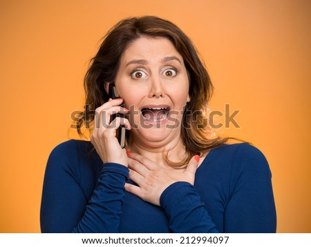 Closeup portrait young shocked business woman funny looking employee talking on cell phone having unpleasant conversation isolated orange background. Negative human emotion, facial expression reaction - stock photo