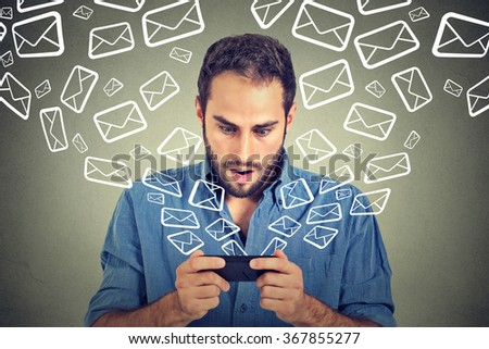 Closeup portrait young shocked man busy sending messages emails from smart phone email icons flying of mobile phone isolated on gray wall background. Telecommunications, internet, data plan concept - stock photo
