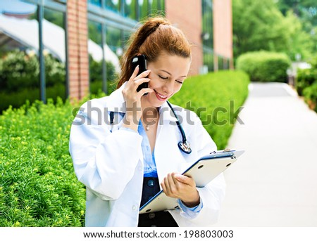 Closeup portrait, young smiling confident female doctor, healthcare professional talking on phone, giving consultation isolated background hospital campus. Patient visit health care. Positive emotions - stock photo
