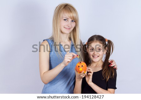 Closeup portrait young smiling girl holding piggy bank, happy mother, older sister deposits money, isolated grey background. Smart financial investment wealth decisions. Budget management, savings - stock photo