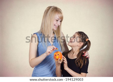 Closeup portrait young smiling girl holding piggy bank, happy mother, older sister deposits money isolated light black background. Smart financial investment wealth decisions. Budget management saving - stock photo