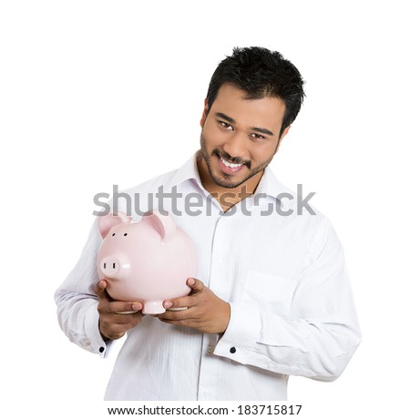 Closeup portrait, young smiling school student, worker man holding piggy bank, isolated white background. Smart currency financial investment wealth decisions. Budget management and savings - stock photo