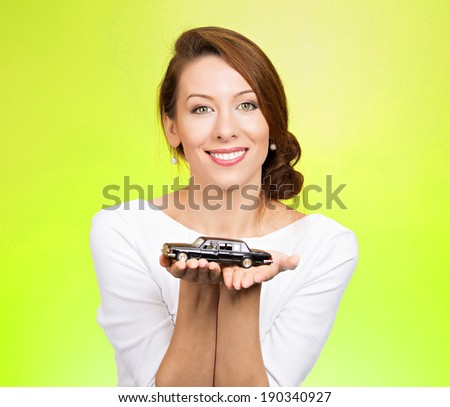 Closeup portrait, young woman, dealership, customer service agent holding model black car, offering credit line, lease deal, new inventory isolated green background. Automobile purchase, financing. - stock photo