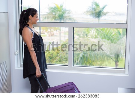 Closeup portrait, young woman in black shirt holding maroon suitcase, packed and ready to go, looking out glass window with palm trees background - stock photo
