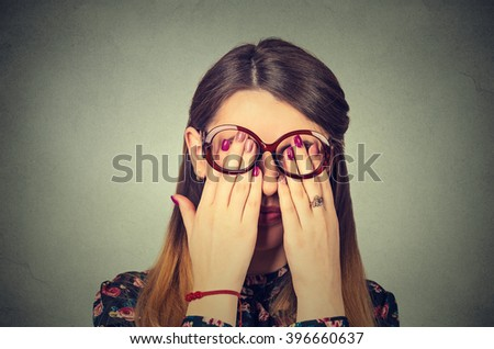 Closeup portrait young woman in glasses covering face eyes using her both hands isolated on gray wall background - stock photo
