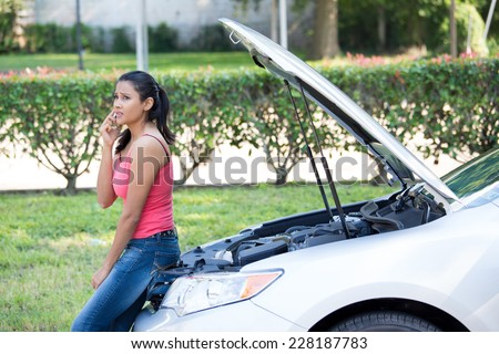 Closeup portrait, young woman in pink tanktop having trouble with her broken car, opening hood and calling for help on cell phone, isolated green trees and shrubs outside background - stock photo