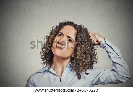 Closeup portrait young woman scratching head, thinking daydreaming about something wondering looking up isolated on grey wall background. Human facial expressions, emotions, feelings, signs, symbols - stock photo