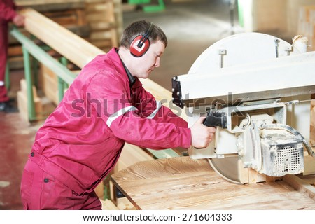 Closeup process of carpenter worker with circular saw machine at wood beam cross cutting during furniture manufacture - stock photo