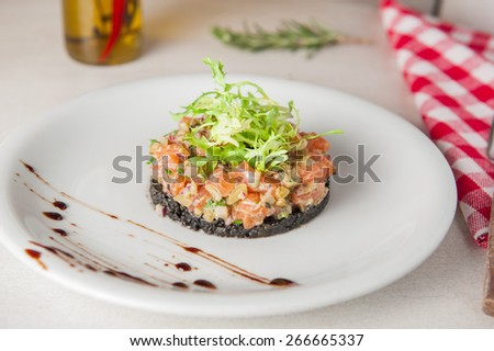 Closeup Raw salmon tartare with mixed vegetables decorated with lettuce mix on the white plate. Gourmet Food - stock photo