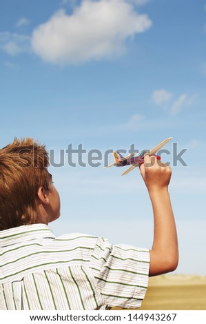 Closeup rear view of a boy flying toy airplane on beach - stock photo