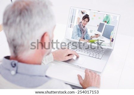 Closeup rear view of a grey haired man using laptop at desk against artist drawing something on graphic tablet with colleagues behind - stock photo