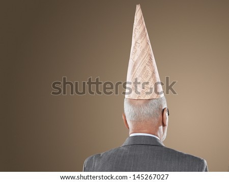 Closeup rear view of a middle aged businessman wearing dunce hat against brown background - stock photo