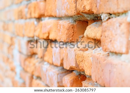 Closeup red brick: old uneven brick wall. - stock photo