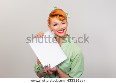 Closeup red head young woman pretty pinup girl green button shirt smiling holding computer blinking looking at you camera isolated yellow background retro vintage style. Human emotions body language - stock photo