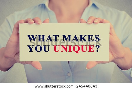 Closeup retro image businesswoman female executive hands holding white sign or card with message text phrase what Makes You Unique? isolated on gray office wall background - stock photo