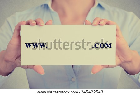 Closeup retro vintage style image business woman hands holding white sign card with www. com written on it with empty space ready for your text website domain isolated on gray office wall background - stock photo