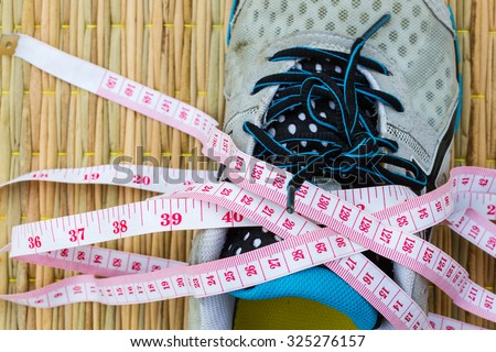 closeup running shoe with measuring tape, Health and Fitness Concept. Selective focus. - stock photo
