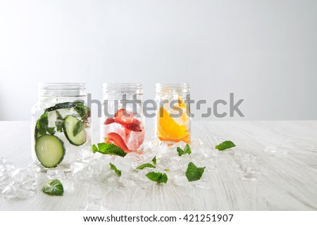 Closeup rustic jars in crashed ice cubes with orange,strawberry,cucumber and mint prepared to make fresh homemade lemonade with sparkling water Healthy beverage to cool down in summer - stock photo