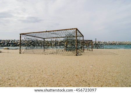 closeup rusty crab pots on the sandy beach white cloudy sky. focus in the middle - stock photo