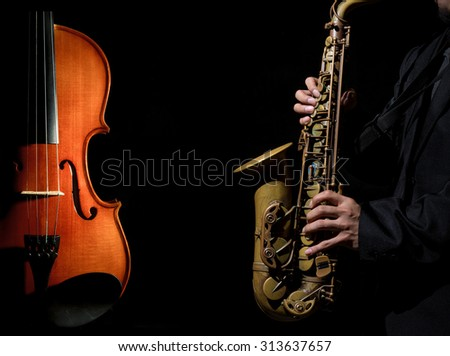 Closeup saxophone in player action with Violin orchestra musical instruments on black background - stock photo