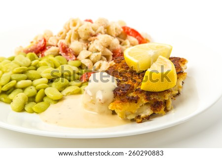 Closeup Selective Focus on Baked Breaded Codfish Dinner lima beans and pasta salad against white background. - stock photo