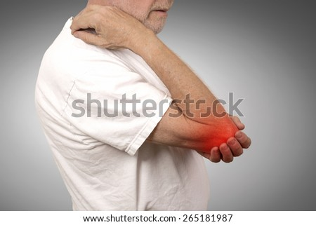 Closeup senior man with elbow inflammation colored in red suffering from pain and rheumatism isolated on gray wall background  - stock photo