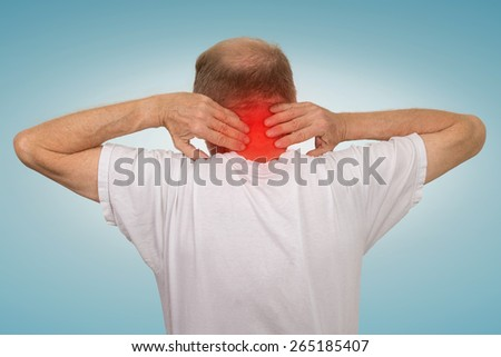 Closeup senior mature man with bad neck spasm pain touching colored in red inflamed area suffering from arthritis isolated on light blue background. Human health problems, geriatrics medicine concept  - stock photo