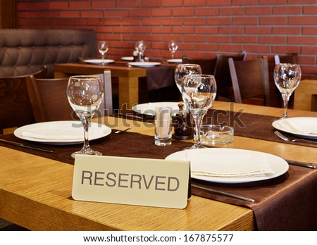 Closeup served table with sign Reserved in cafe - stock photo