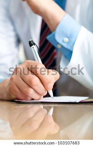 Closeup shot of a doctor writing a medical recipe - stock photo